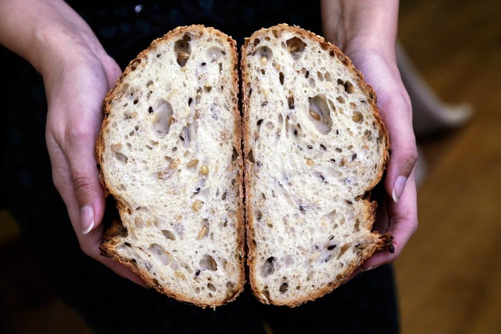 Hand modeling Brasserie Bread's harvest grain loaf. Photo by Rhys Newling.